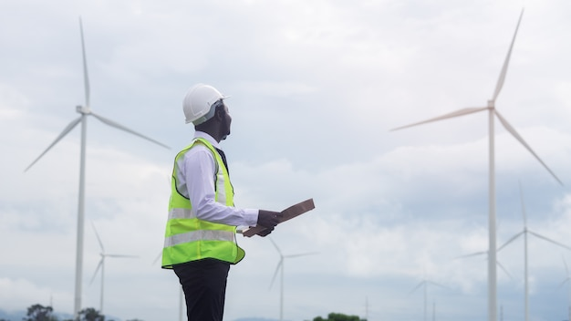 風力タービンで立っているアフリカのエンジニア