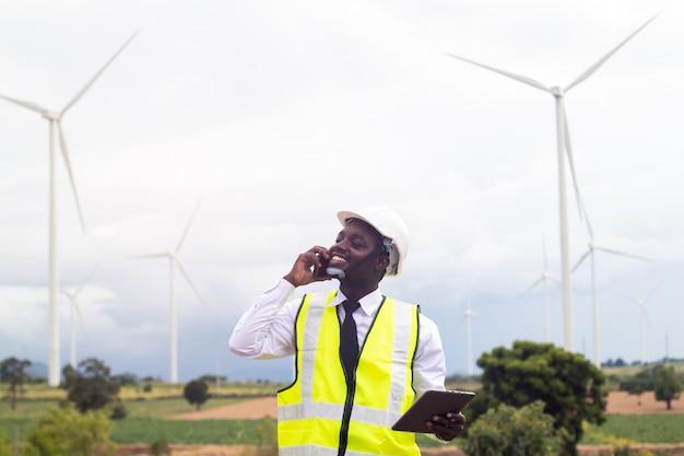 風力タービンと立っていると話しているスマートフォンのアフリカのエンジニア