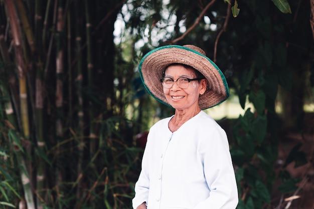 緑の自然な背景を持つ笑顔アジア農家高齢者女性の美しい肖像画。