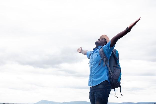 山の景色のバックパックを持つ自由アフリカ観光旅行者男