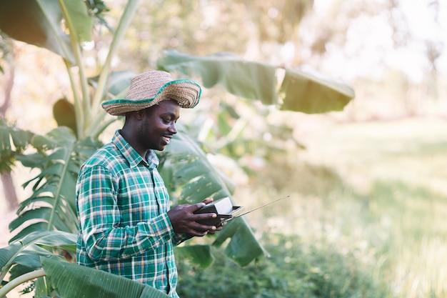 農場でビンテージラジオを保持しているアフリカの農夫男