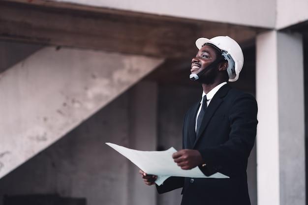 未完成の建物を見ているエンジニアのアフリカ人
