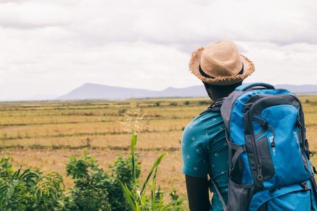 山の景色にバックパックを持つアフリカの観光旅行者男。ビンテージスタイル