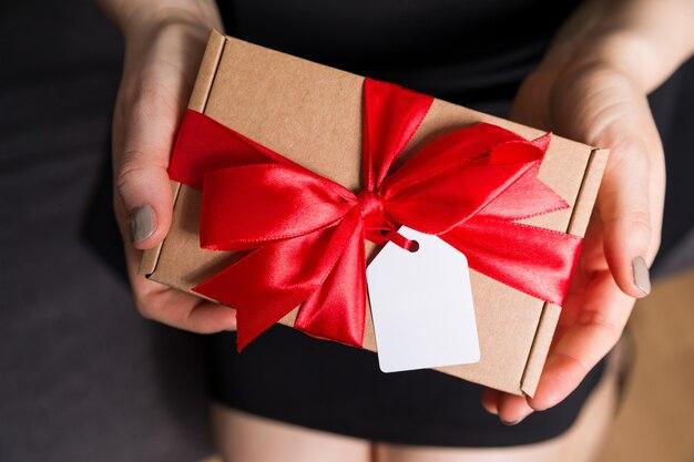 バレンタインの日ギフトタグと弓のクローズアップ - プレゼントを手で保持している女性