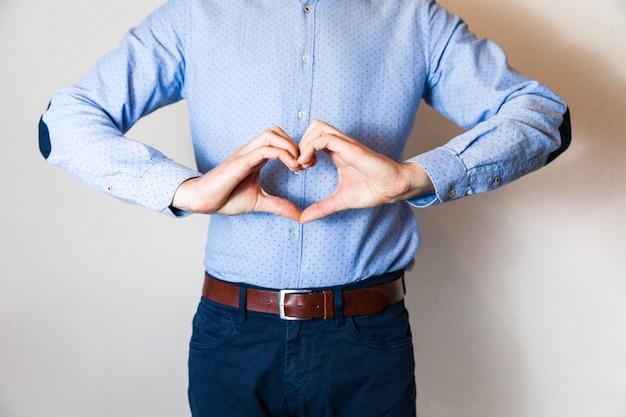 Красивый молодой человек, делая форму сердца с пальцами руки, любовь, отношения, знакомства.