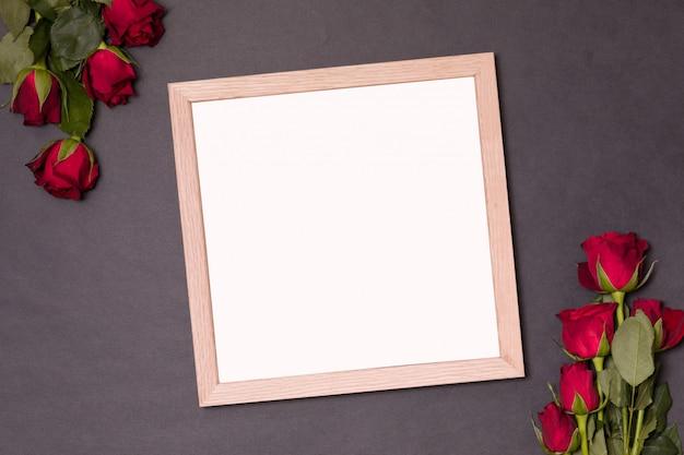 テキストのための空のスペースを持つフレーム - バレンタインデーは赤いバラでモックアップします。
