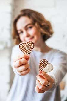 По-европейски выглядящая девушка держит печенье в форме сердца, любовники, день святого валентина, выпечка, кулинария