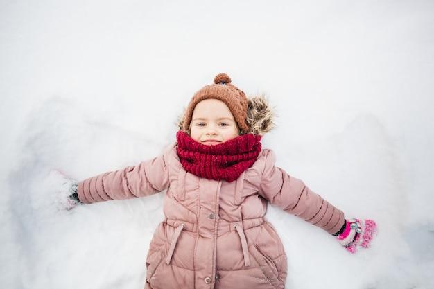 冬と少女は雪の上に横たわって、子供たちのゲーム、散歩と楽しい、暖かい服