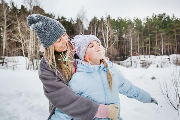 母と娘の冬の森、冬の木、花輪、森の中の休日を歩く