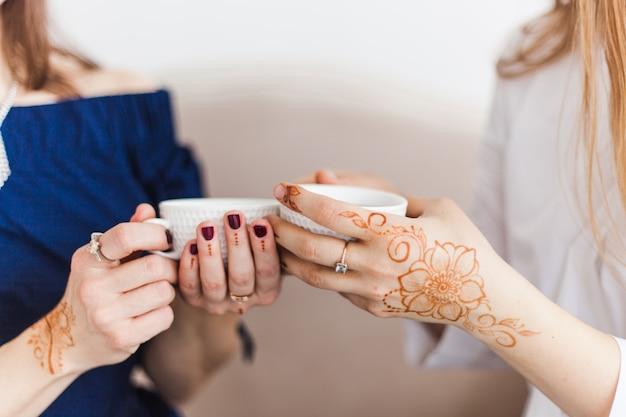 В руках чашка чая или кофе, напиток по утрам, обед, руки покрыты традиционным узором, махенди, рисунок на руках