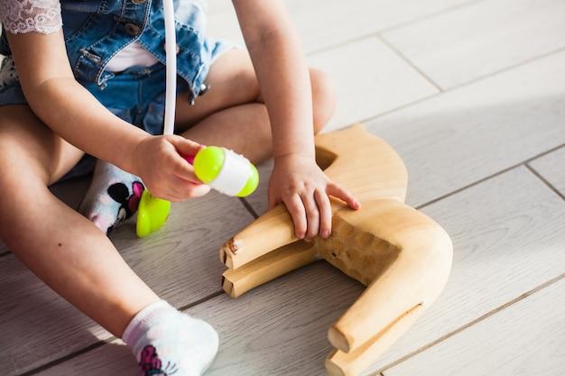 ヨーロッパの外観の小さな女の子が床に座って、医者、クマとおもちゃの治療、精神性、脳と子供の発達、母親を演じます