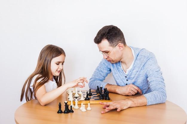 Девочка и папа играют в домашнюю игру, в шахматы, головоломку для развития мозга, умственный интеллект
