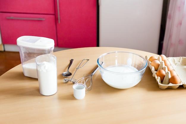 キッチンとテーブル、ベーキング、小麦粉のボウル、牛乳、砂糖、おいしい家族向けの朝食、子供と一緒に料理