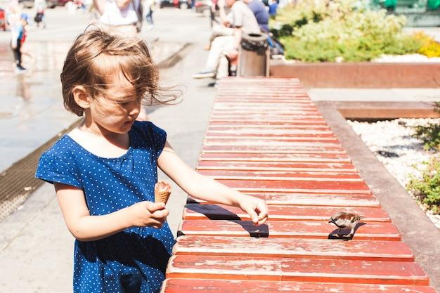 小さな女の子が鳥、スズメ、動物と子供、アイスクリーム、街と夏にパンを与えます