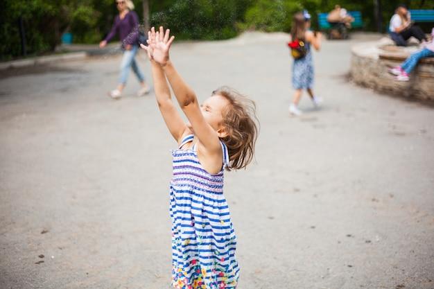 短い髪とドレスを着た小さな女の子が夏に公園で遊んで、シャボン玉をキャッチし、笑い、感情、子供時代、友達とチャット