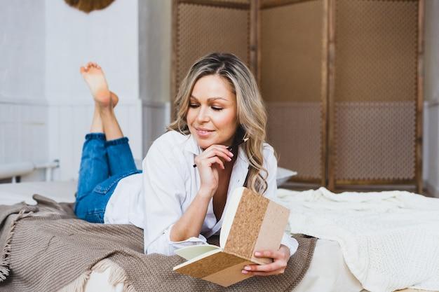 ヨーロッパ風の女の子がマットレスの上に座って、白いブラウス、ジーンズ、ファッション、美容、スタイル、日記、メモ帳を書いています。