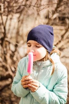 Девушка на улице есть мороженое, шапка, весна, прохлада, сладость, вкус, детство