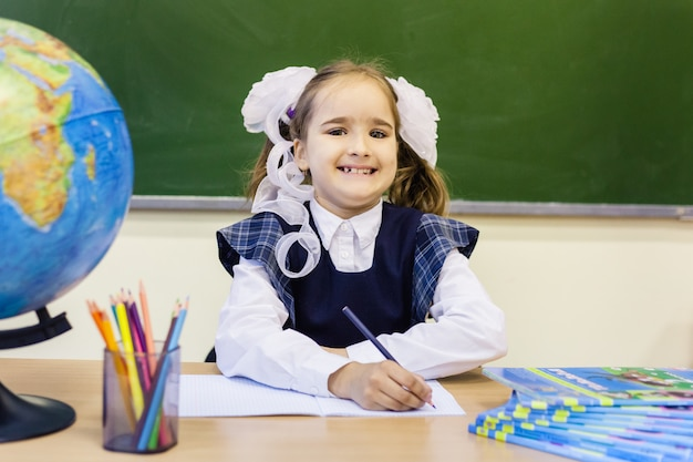 女子高生と学校。少女は学校で制服を着ています。トレーニング
