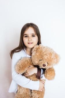 お気に入りのテディベア、幼年期および心配、家族および友人を持つ少女。女の子の演奏とおもちゃを抱いて
