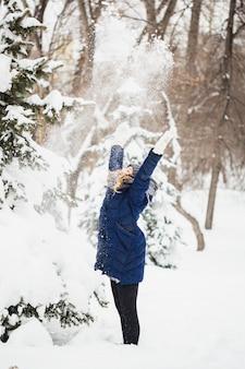 Девушка в зимнем парке покрыта снегом