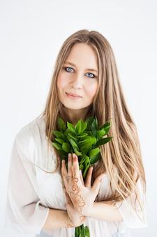 Девушка европейской внешности в яркой одежде с зелеными ветками.