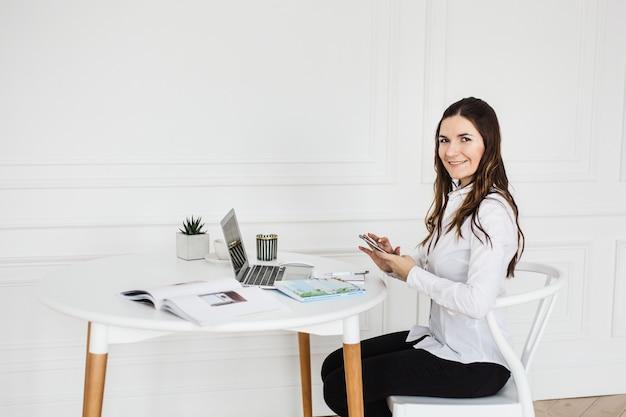 コンピューターで作業して、仕事、ブログ、レジャー、エンターテイメントにコンピューターを使用している女の子