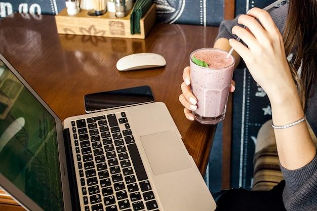カクテルを片手に、カフェに座ってラップトップ、仕事とレジャーのためのパソコンに取り組んでいる女の子