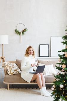 Женщина работает или учится на компьютере, интерьер оформлен на рождество