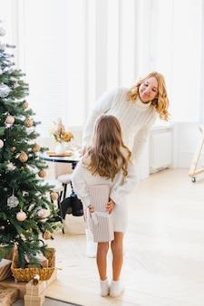 クリスマスツリー、新年とクリスマス、家族と喜び、伝統のために装飾されたインテリアの近くに彼女の母親を持つ少女