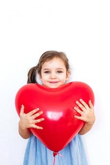 Маленькая девочка держит красивый красный воздушный шар в форме сердца для подарка на день святого валентина, влюбленных, день святого валентина, семьи и сердца