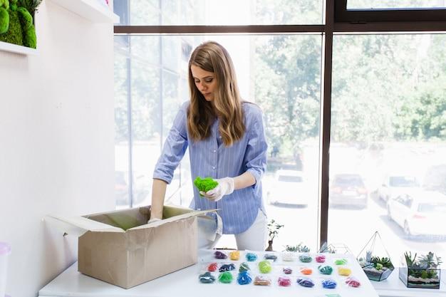 少女デザイナー、デコレーター、苔を扱う花屋、材料の入った箱、苔、植物。事業、インテリア事業
