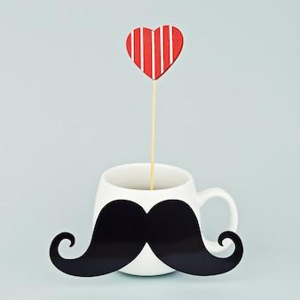 黒い口ひげと赤い心を持つ白いマグカップ