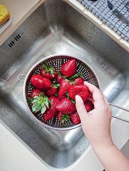 Помыл спелую сочную красную клубнику в сетке