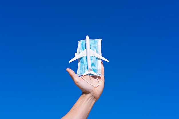Игрушечный самолет и маска для лица в руке