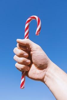 Мужская рука держит традиционную рождественскую полосатую конфету
