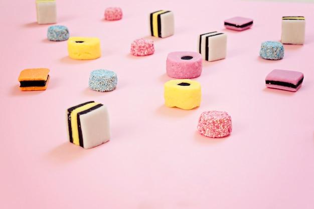 ピンクの背景に着色された歯ごたえのあるキャンディー