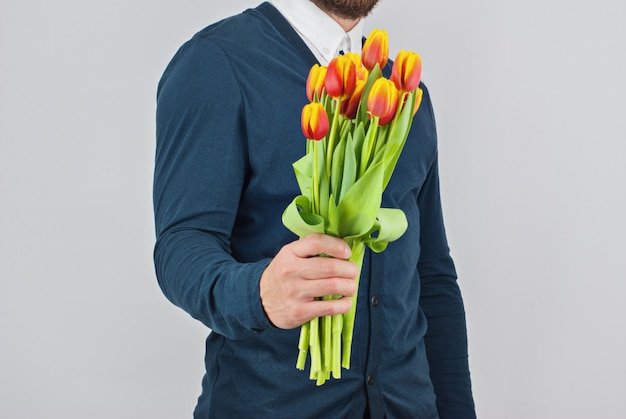 Мужчина с бородой держит букет тюльпанов