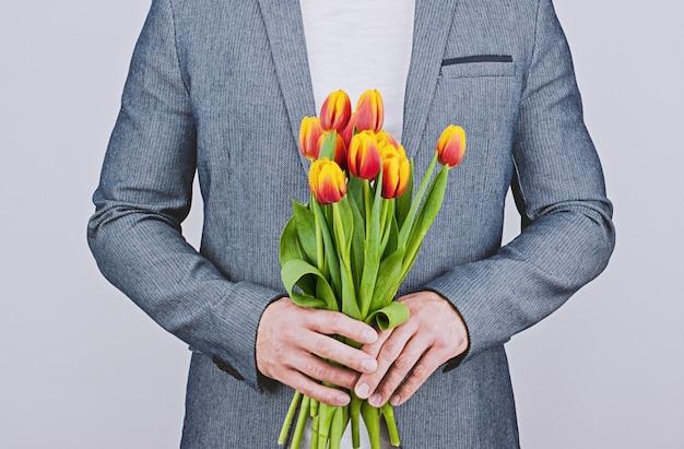 Мужчина в синей куртке держит букет тюльпанов