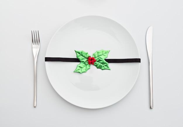 Новогоднее украшение с листьями падуба на белой тарелке