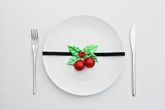 Новогоднее украшение с листьями падуба и красными шариками на белой тарелке