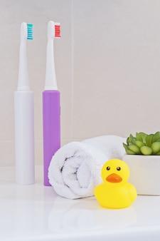 Электрические зубные щетки на раковине в ванной