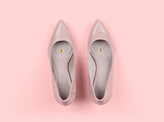 プッシュピンと古典的な女性のベージュの靴のペア