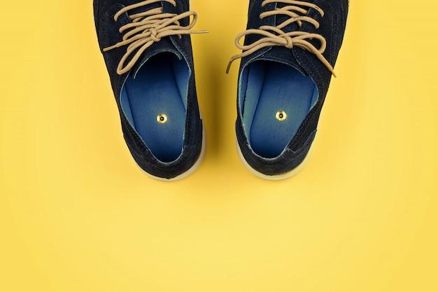 黄色の紙のピンを持つ男性の靴