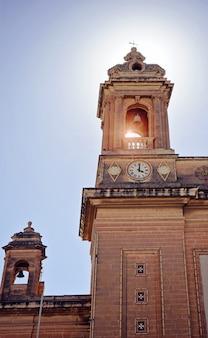 Вид снизу на две башни церкви с колоколом и часами