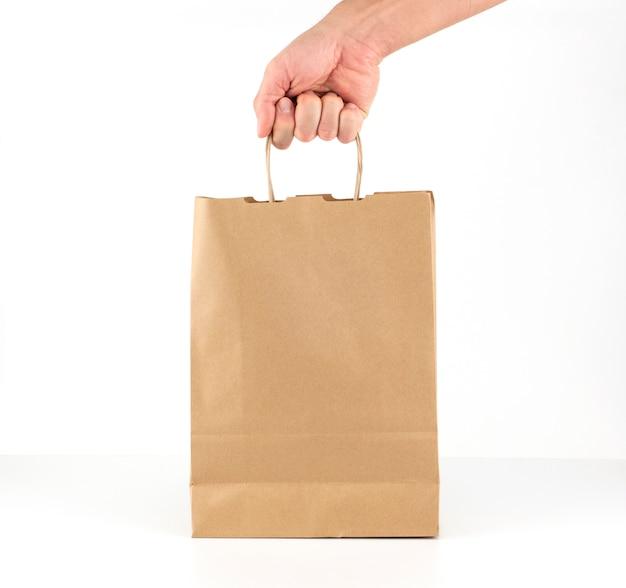 Мужская рука держит бумажный пакет