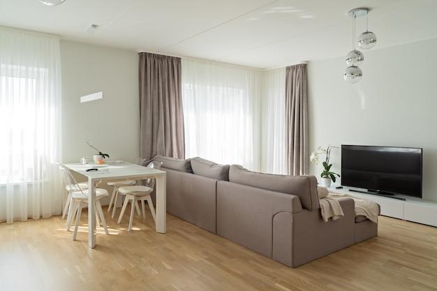 Вид на современную большую и светлую гостиную с удобным бежевым диваном и обеденным столом