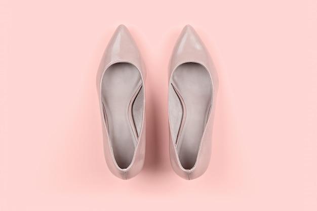 Пара классических женских бежевых туфель на розовом