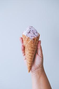 女性の手の指はアイスクリームとワッフルコーンを保持します。