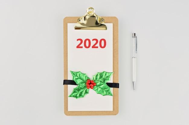 クリスマスの装飾と白のペンで空のクリップボードノート