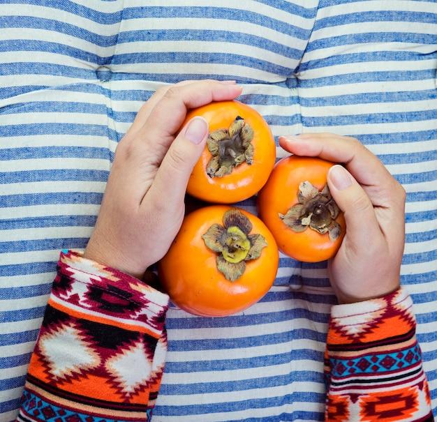 Женская рука держит три спелых хурмы на полосатом синем